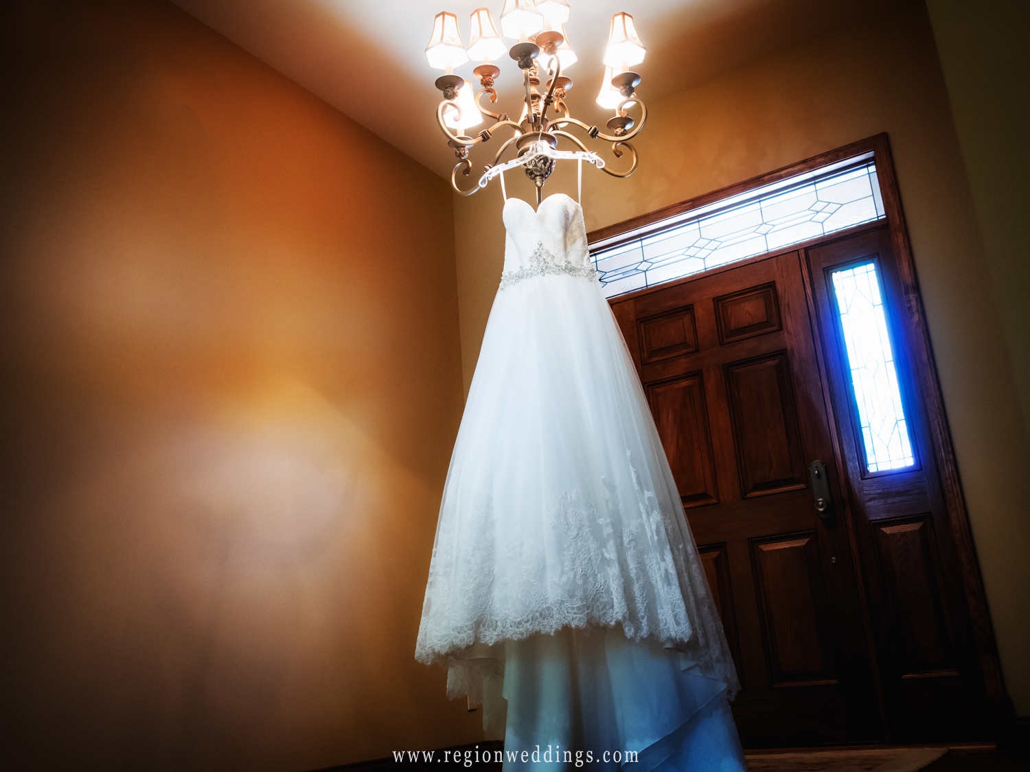 A beautiful wedding dress hangs from a chandelier at Sandy Pines Condo.
