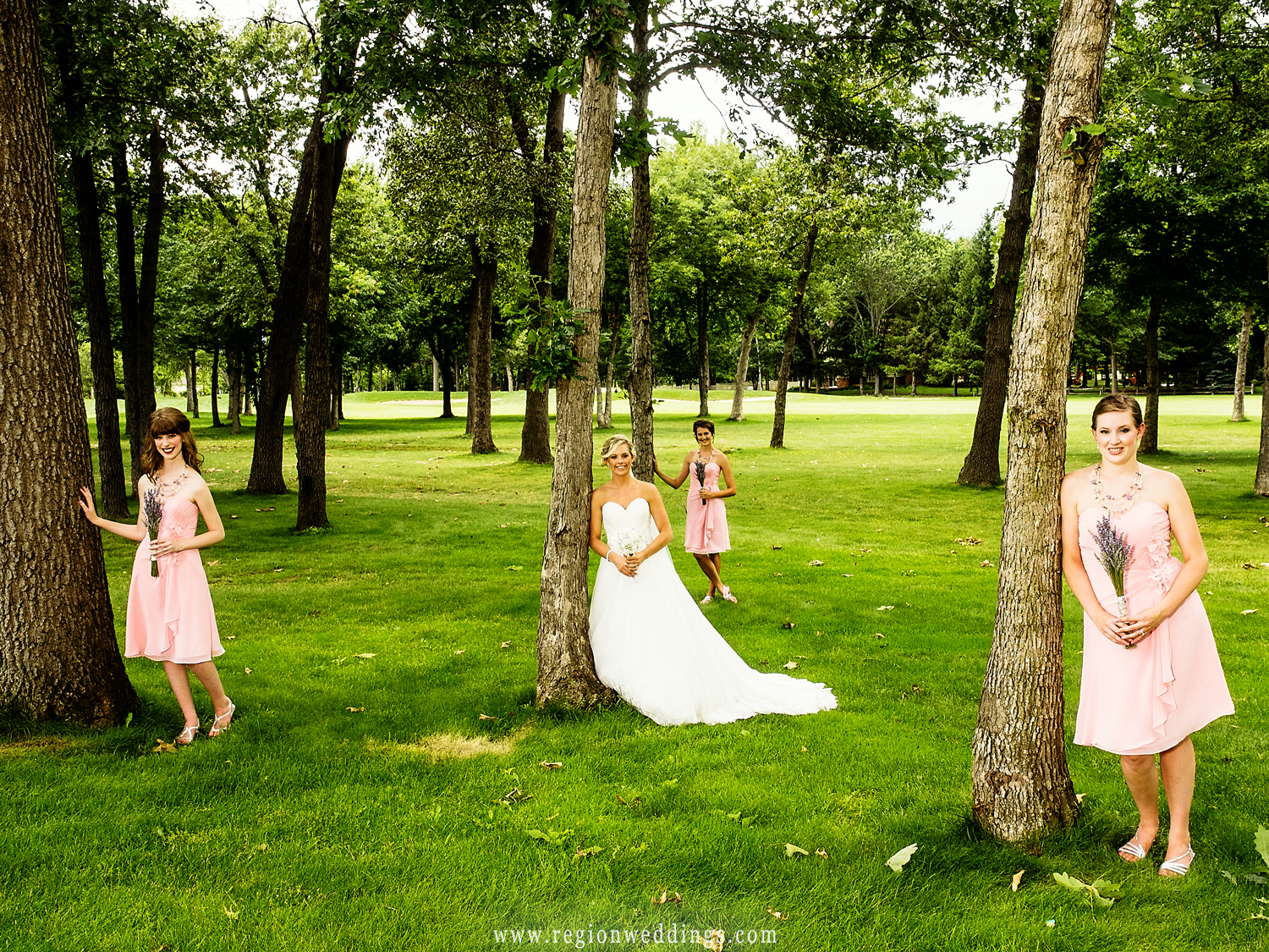 Bridesmaids do some tree hugging at Sandy Pines Golf Course.