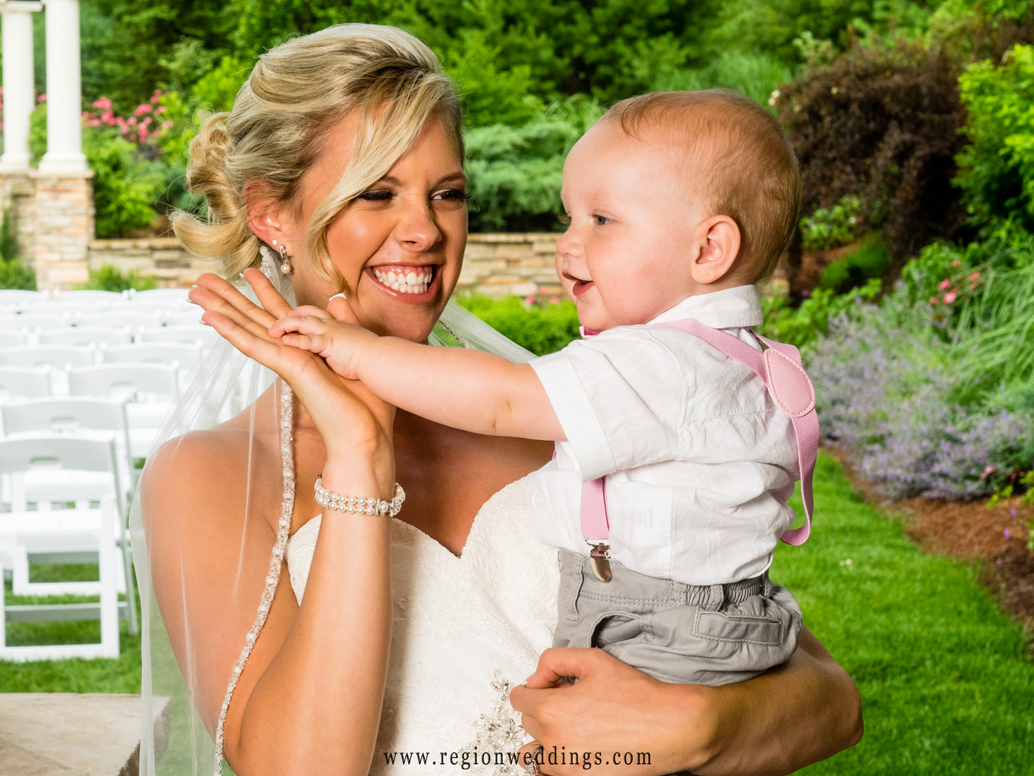The bride high fives a little baby boy at her wedding.