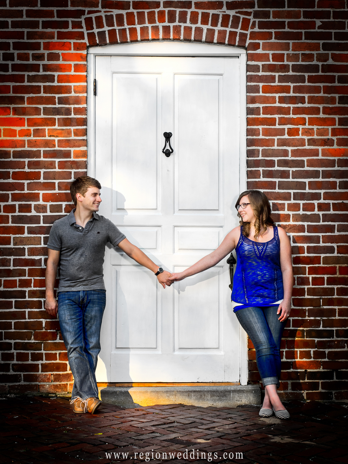 An engaged couple holds hands in between a doorway surrounded by brick at Deep River Park.