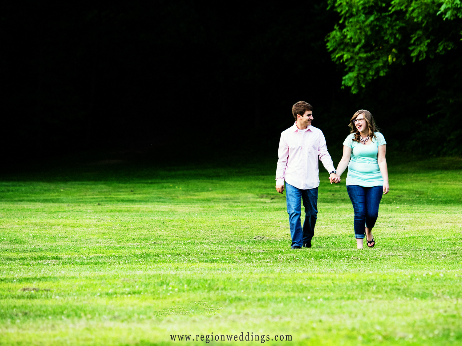 A fun stroll through the grass during an engagement session.