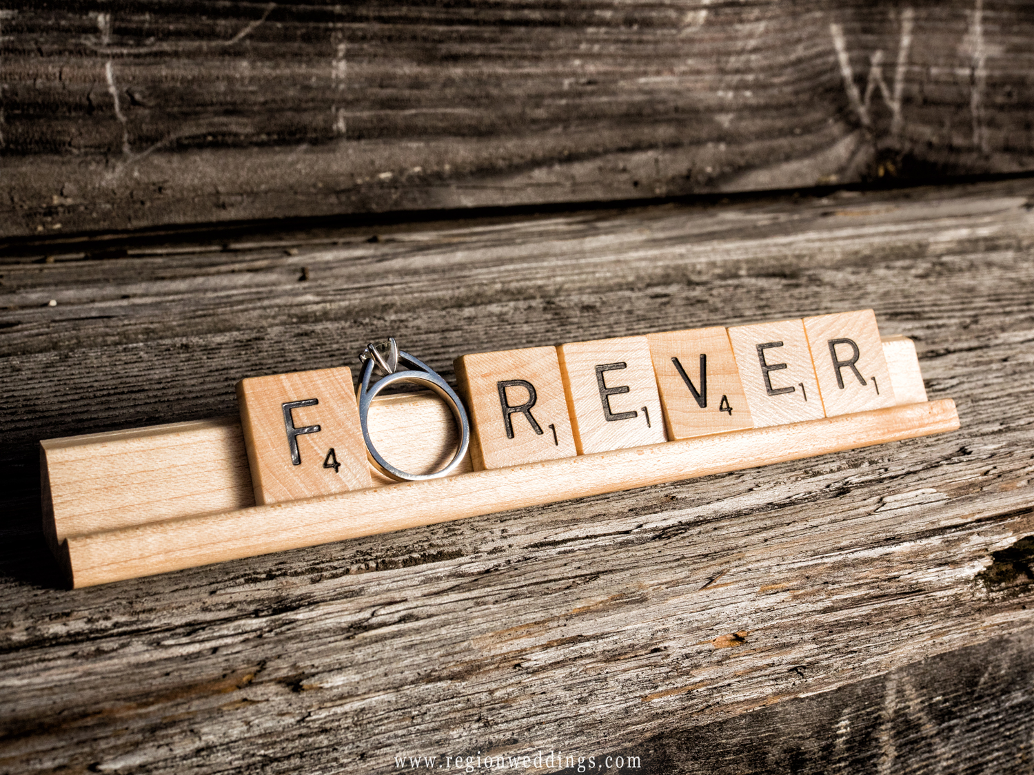 Scrabble letter spell 'forever' with the engagement ring as the letter 'o'.