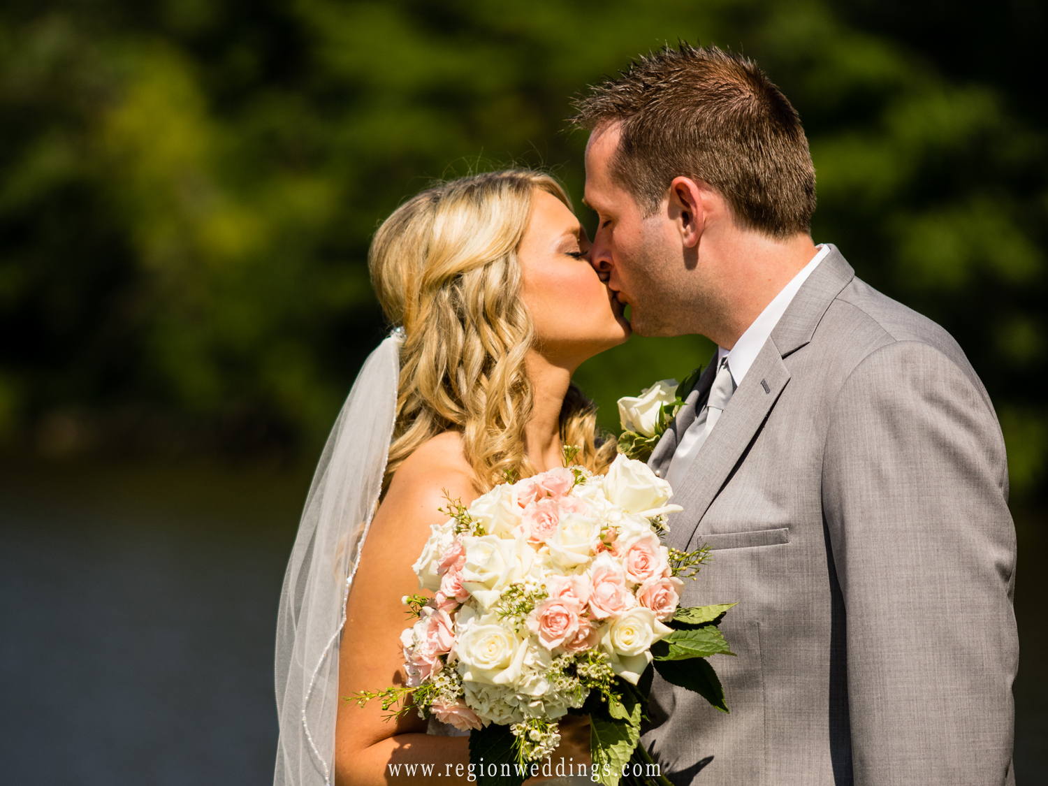 A sun drenched kiss along the lake for the bride and groom.