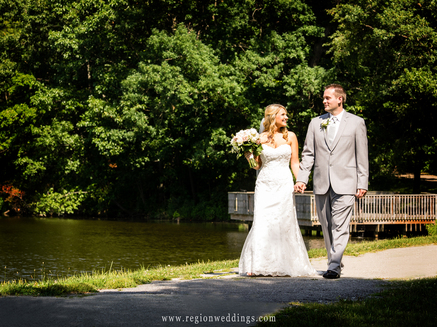 The bride and groom take a romantic stroll along Lemon Lake in Crown Point, Indiana.