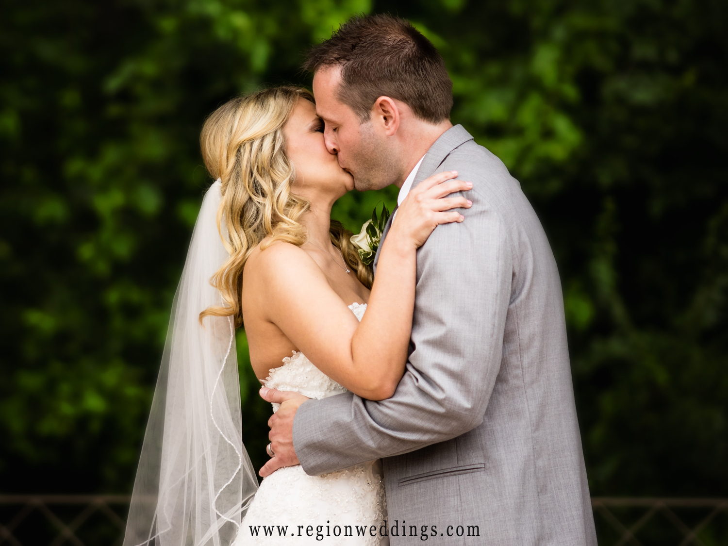 The bride and groom have their first kiss underneather the gazebo at Halls of St. George.