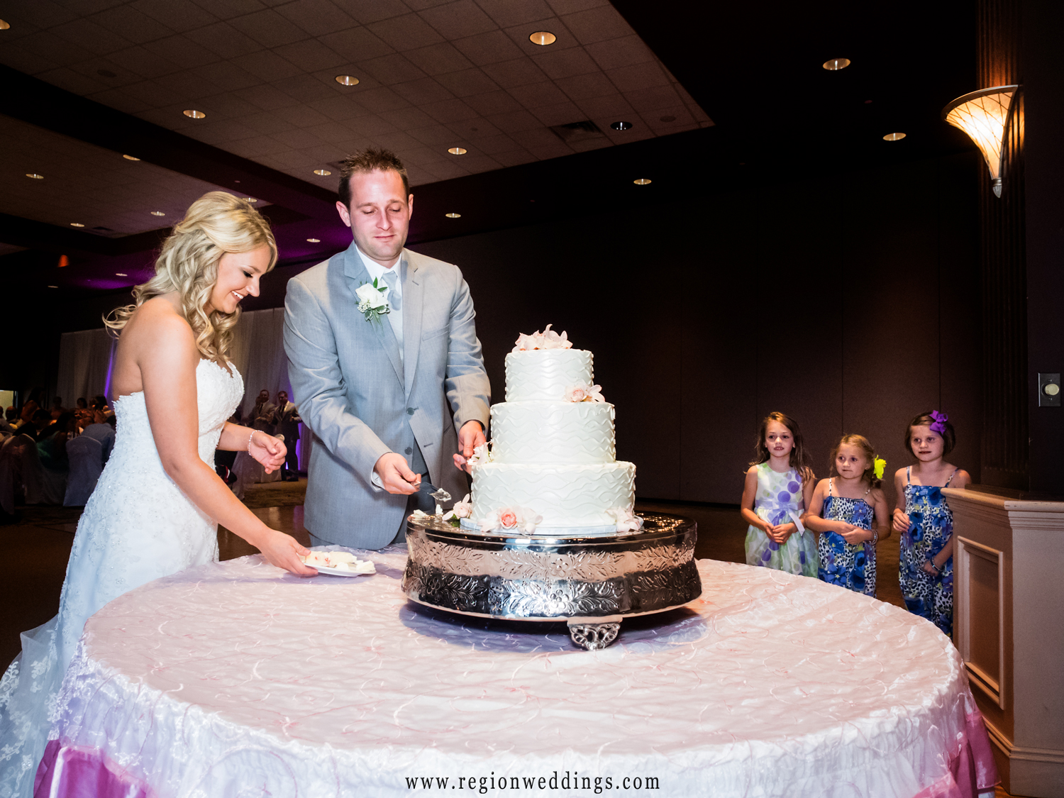 Future brides and future clients photo bomb the couple as they cut their wedding cake.