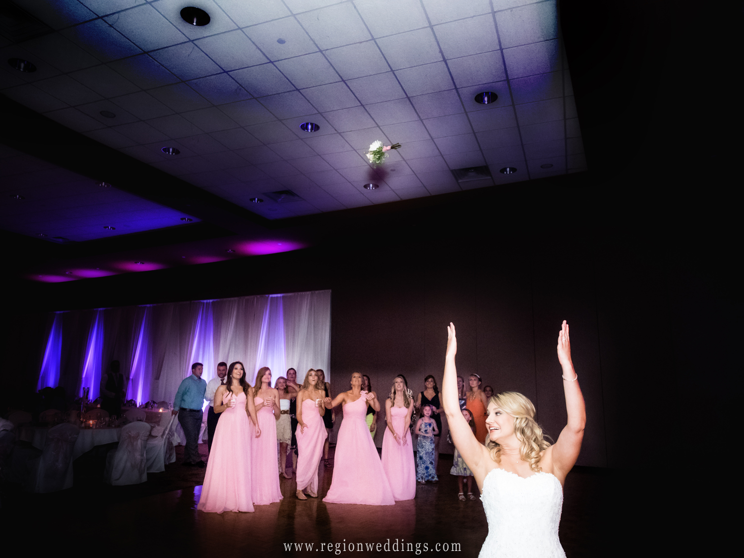 The single girls await the landing of the bouquet.