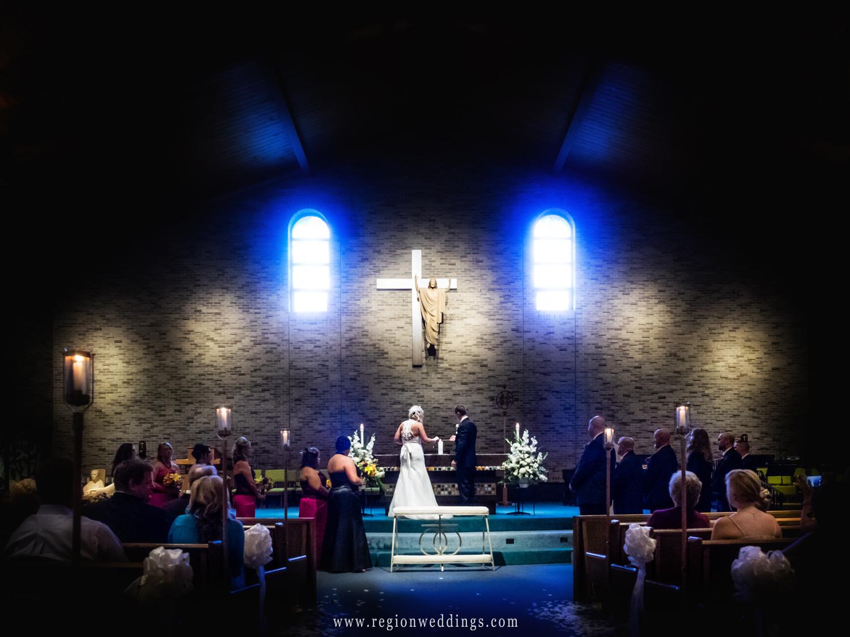 The bride and groom light unity candles at St. Maria Goretti Roman Catholic Church.