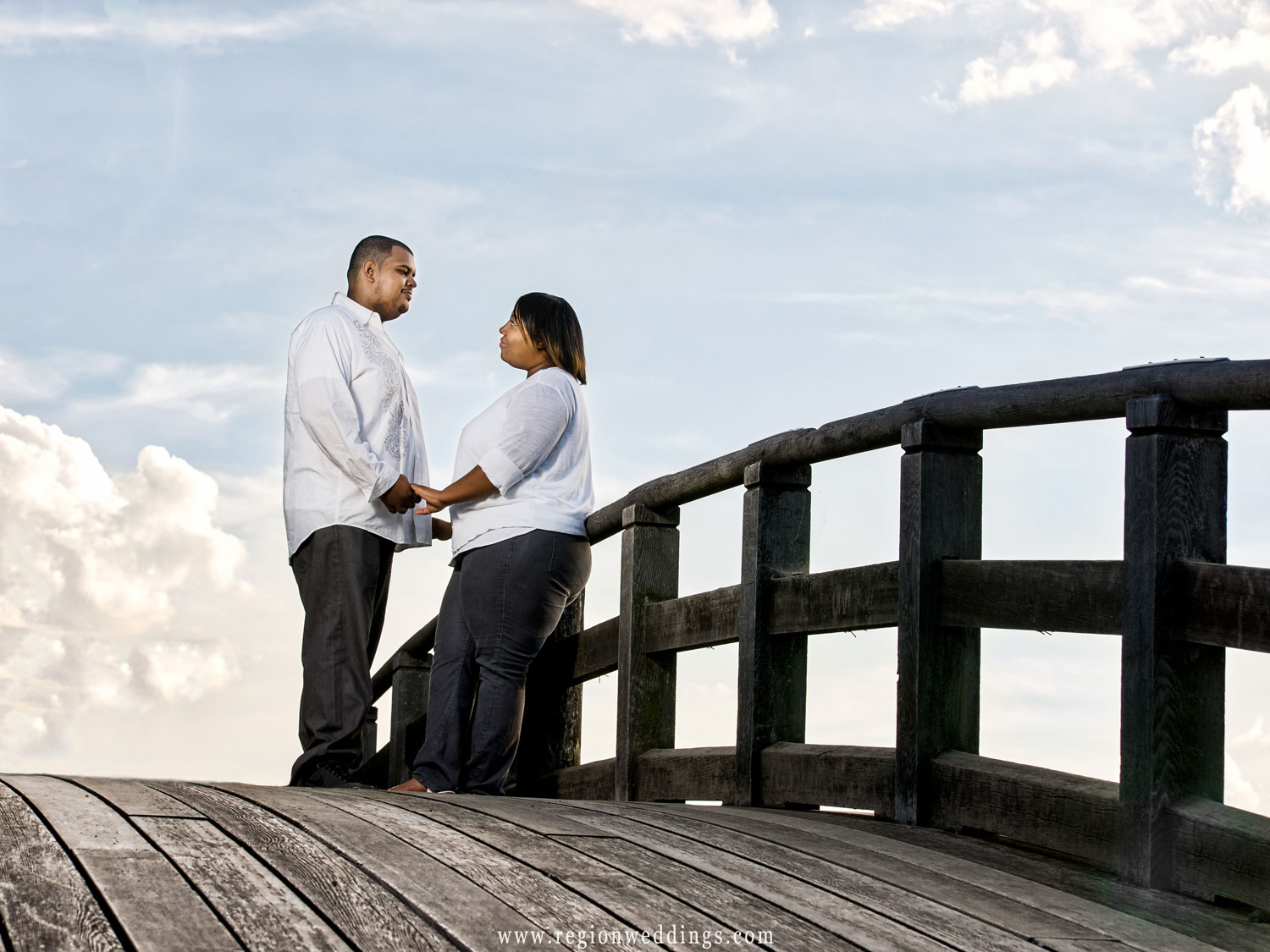 A couple holds hands atop the Marquette Park lagoon bridge.