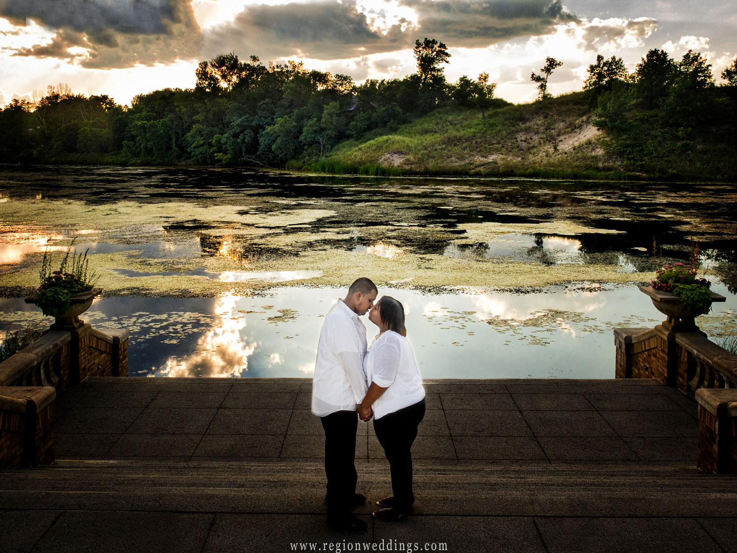 A young couple is about to kiss as the sky reflects into the lagoon water at Marquette Park Pavilion.