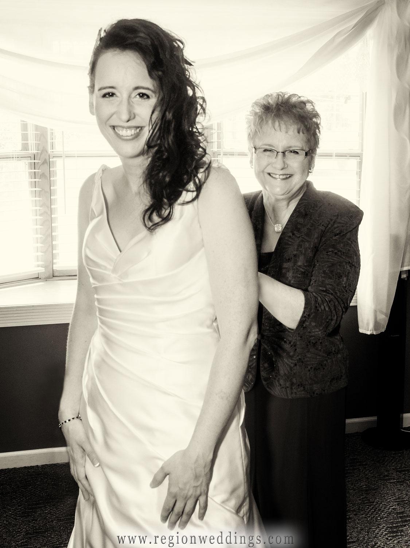 Mom zips up her daughter's wedding dress on wedding day.