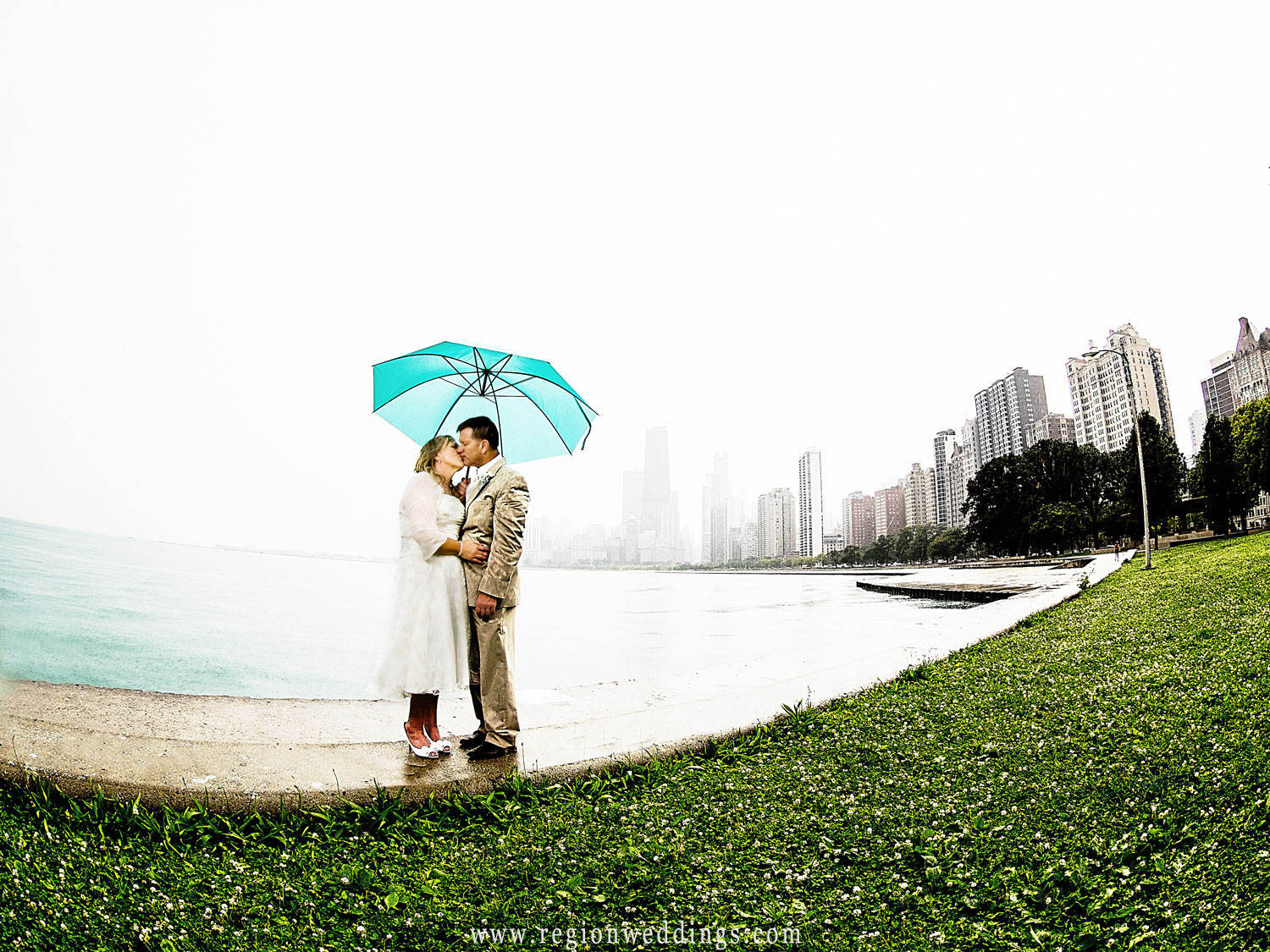 Haze overtakes the Chicago skyline as the bride and groom kiss along Oak Street Beach in Chicago.