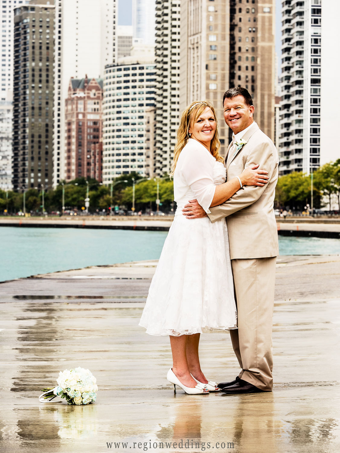 Rain reflects the bride's bouquet on the shore of Lake Michigan in this Chicago wedding photo.