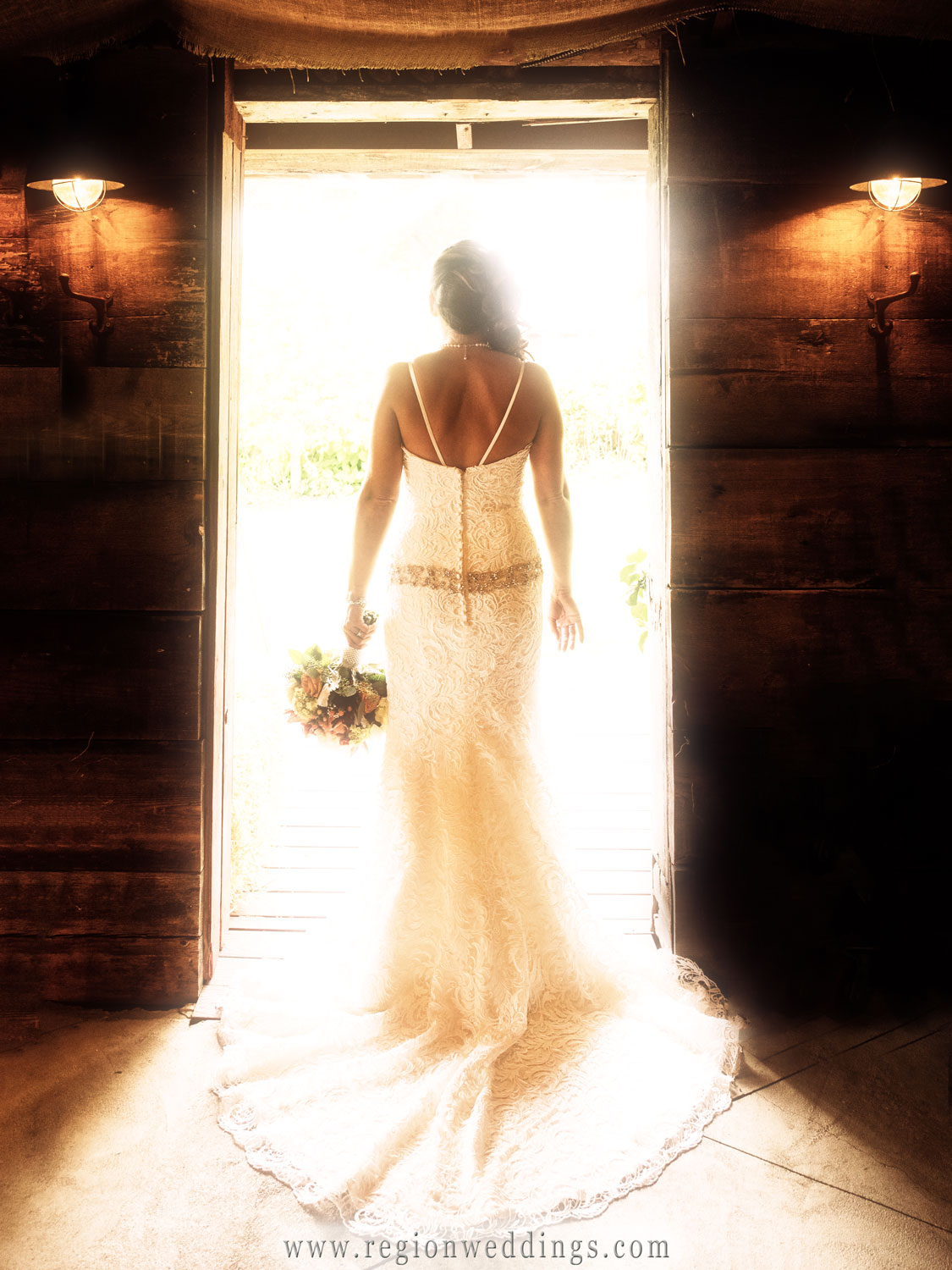 The bride glows in sunlight at the entrance of The Red Barn Experience in LaPort, Indiana.