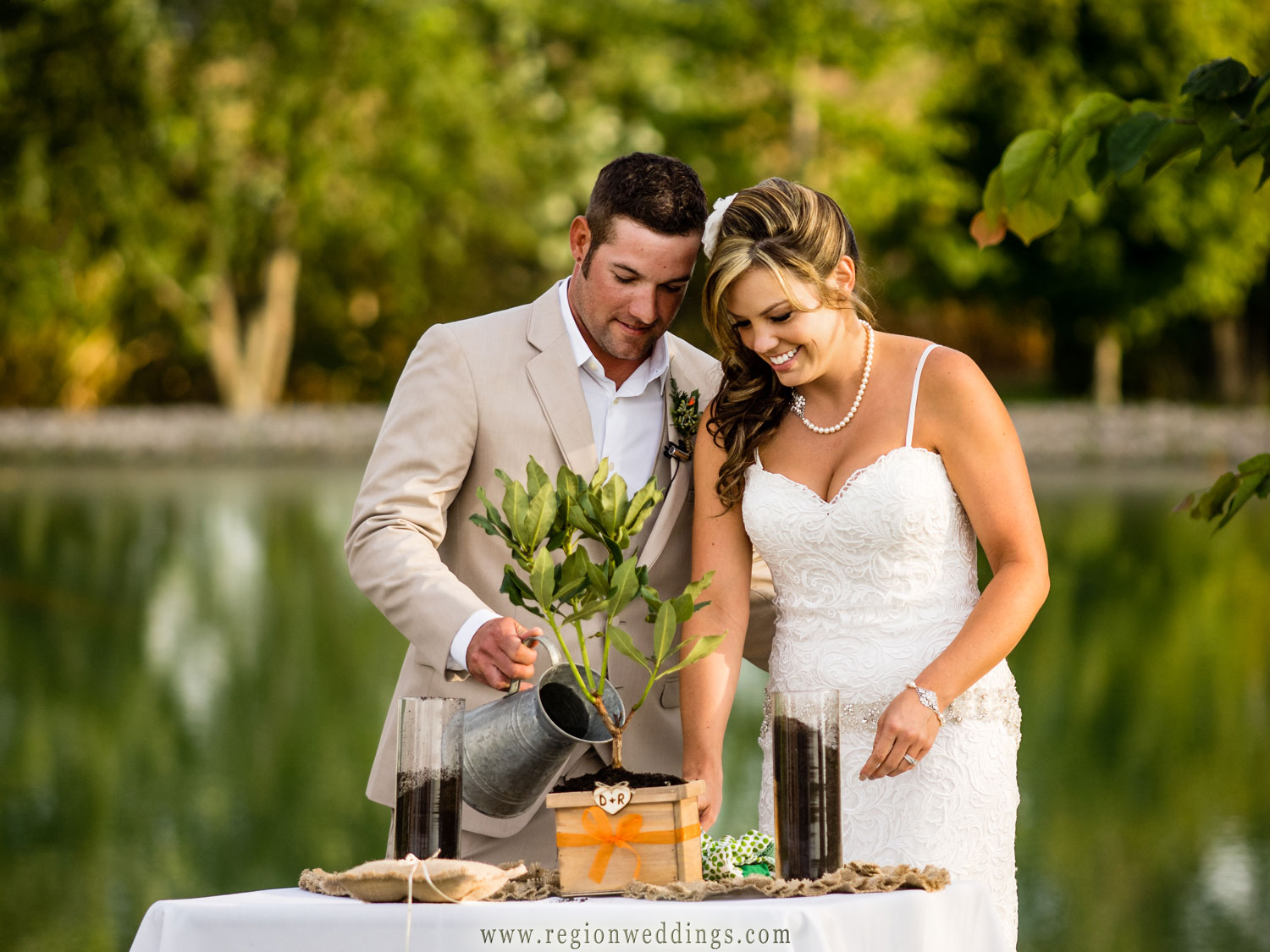 The bride and groom plant a garden together during their outdoor wedding ceremony.