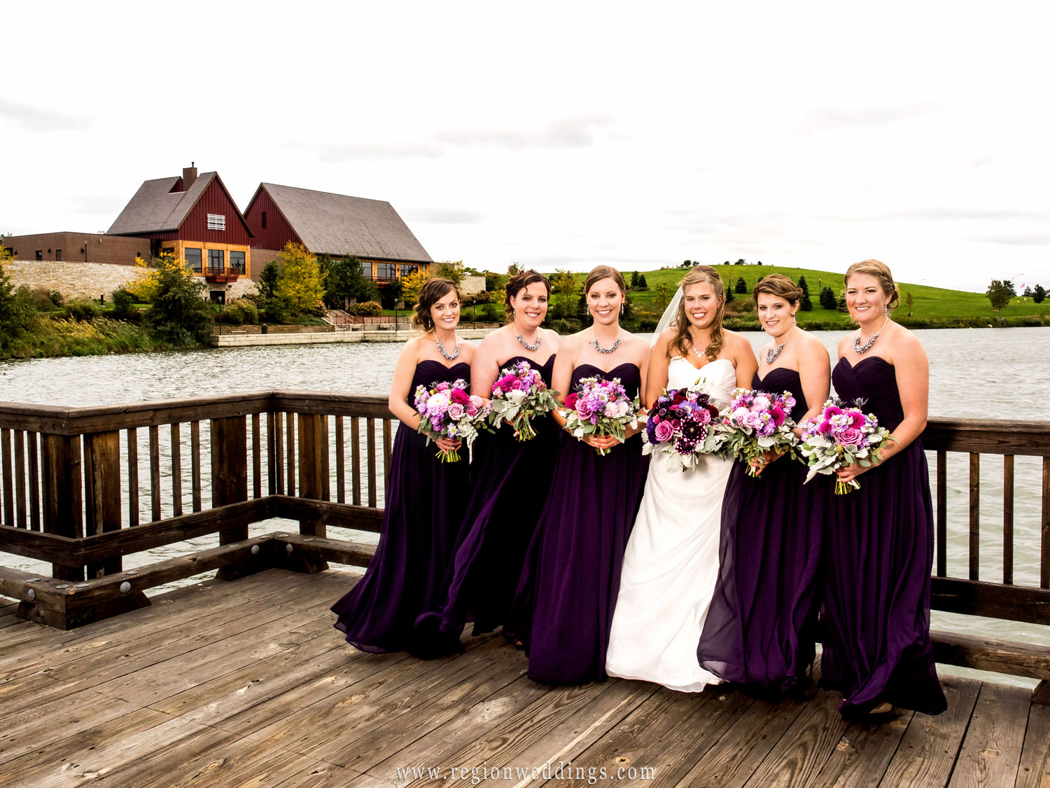 The bridesmaids show off their purple dresses on the bridge that overlooks the Centennial Park clubhouse.