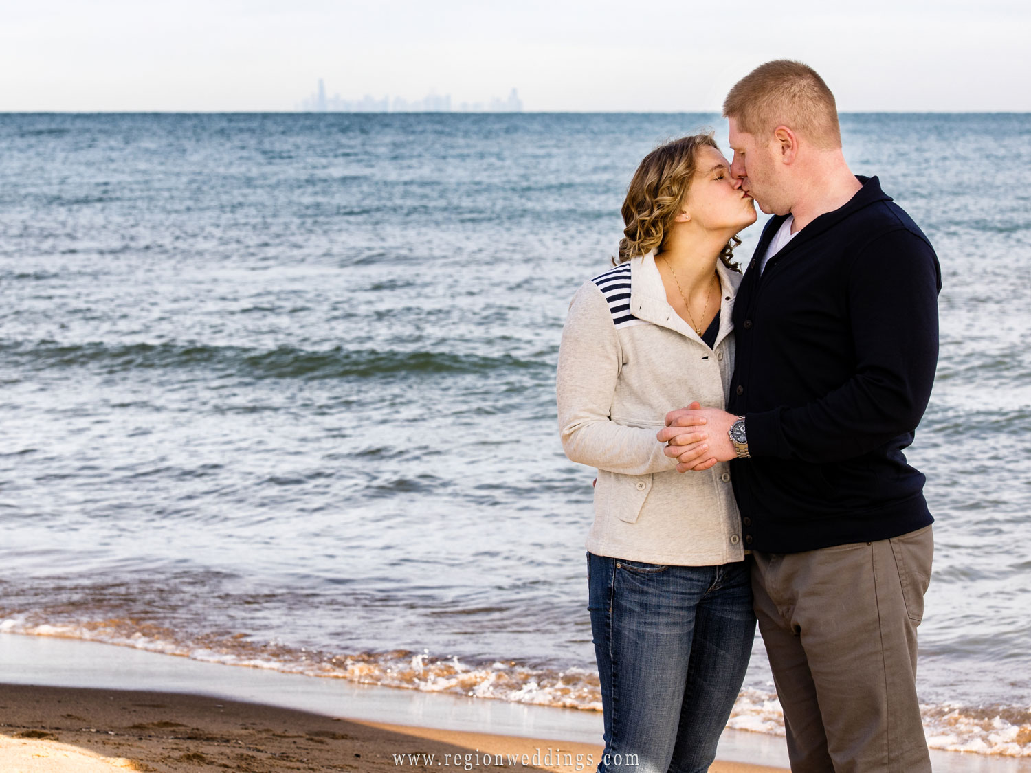 The skyline of Chicago can be seen in the background of this engagement photo along Lake Michigan.