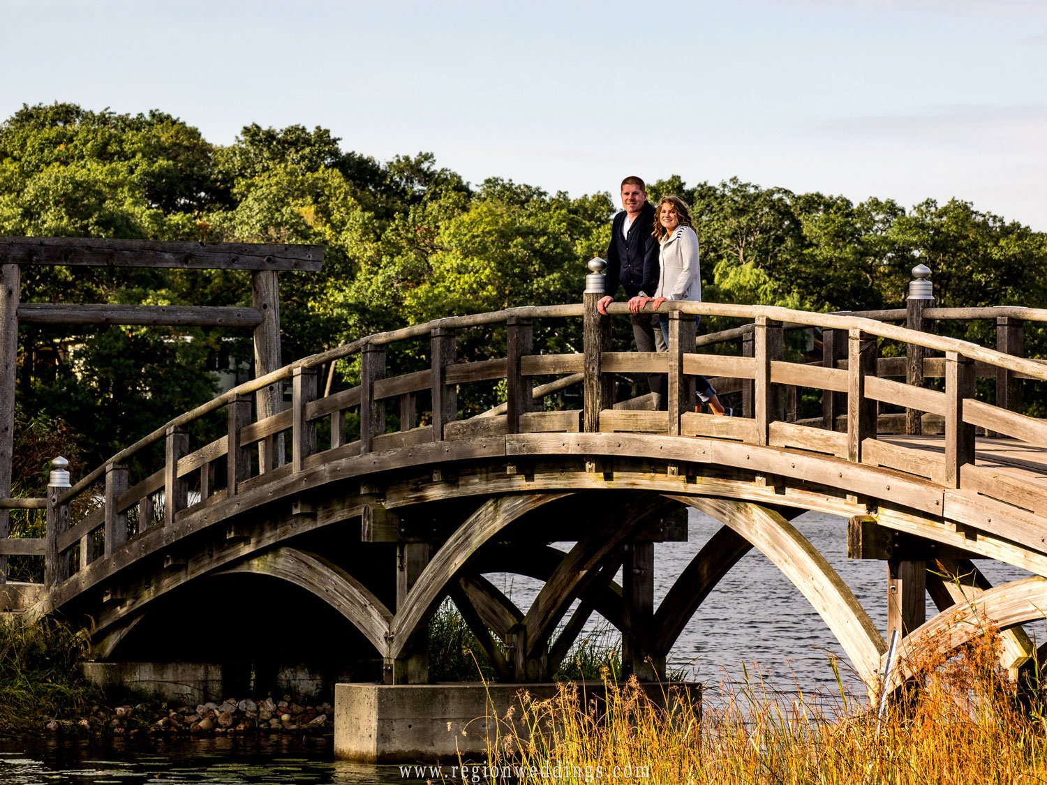 A young couple looks out over the lagoon bridge at Marquette Park.