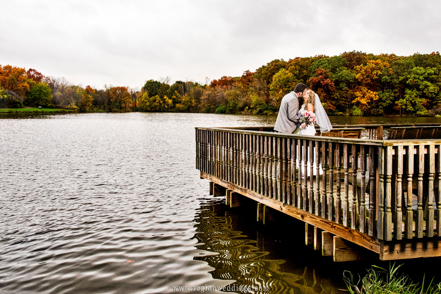 Fall colors pop in the background as the bride and groom kiss on the pier.