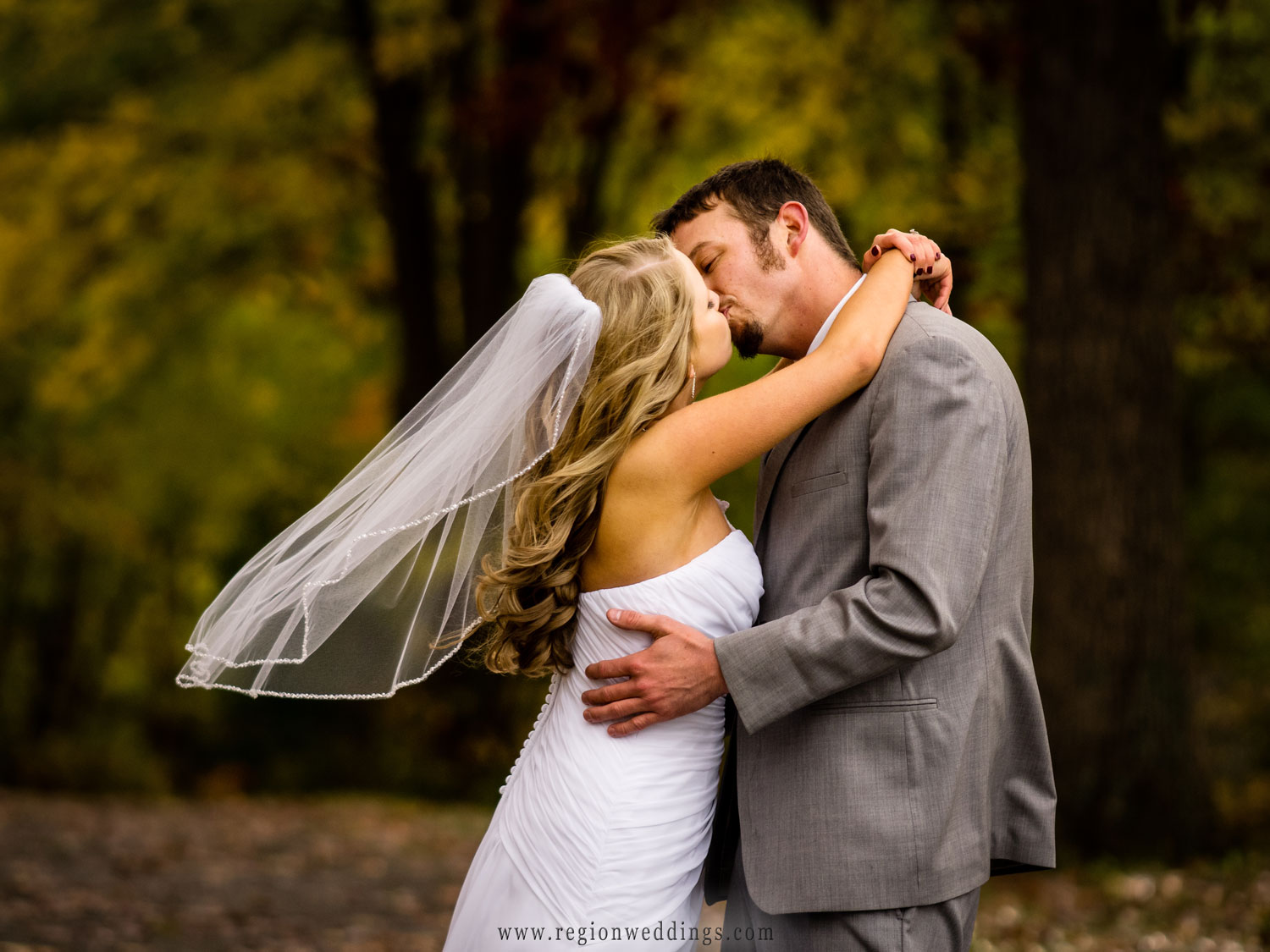 The bride's veil blows in the wind as she kisses her new husband.