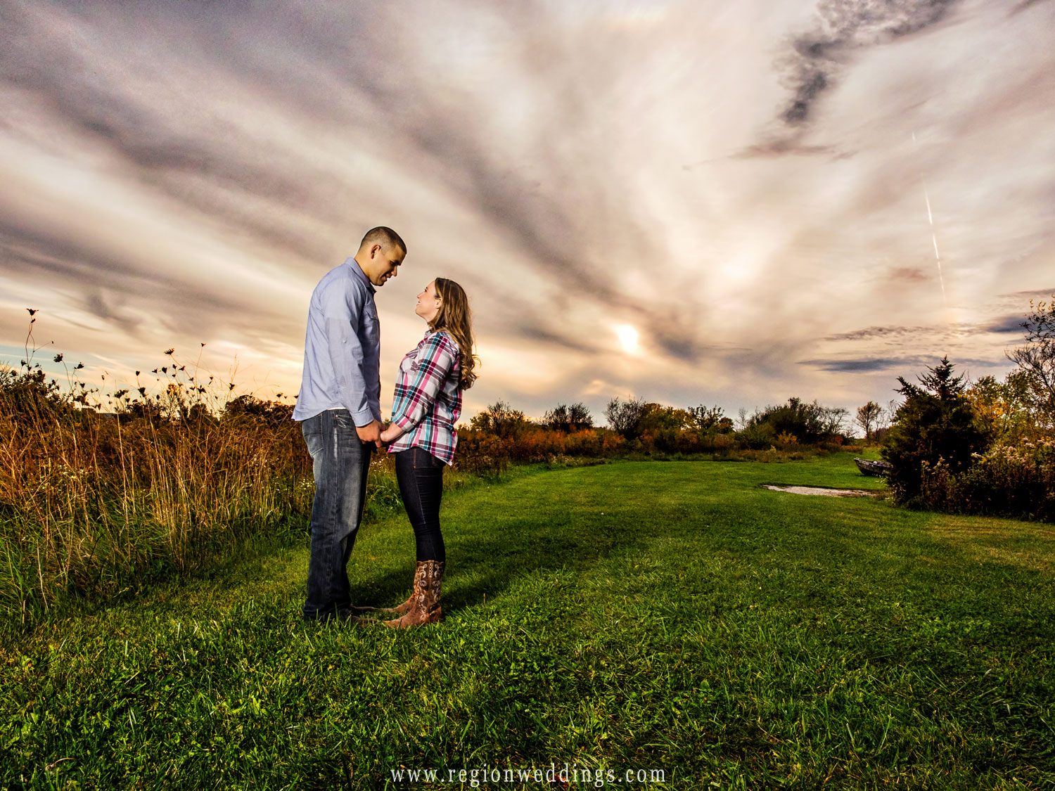Wicked looking clouds swirl in the skies above in this engagement photo taken on a farm in Lowell, Indiana.