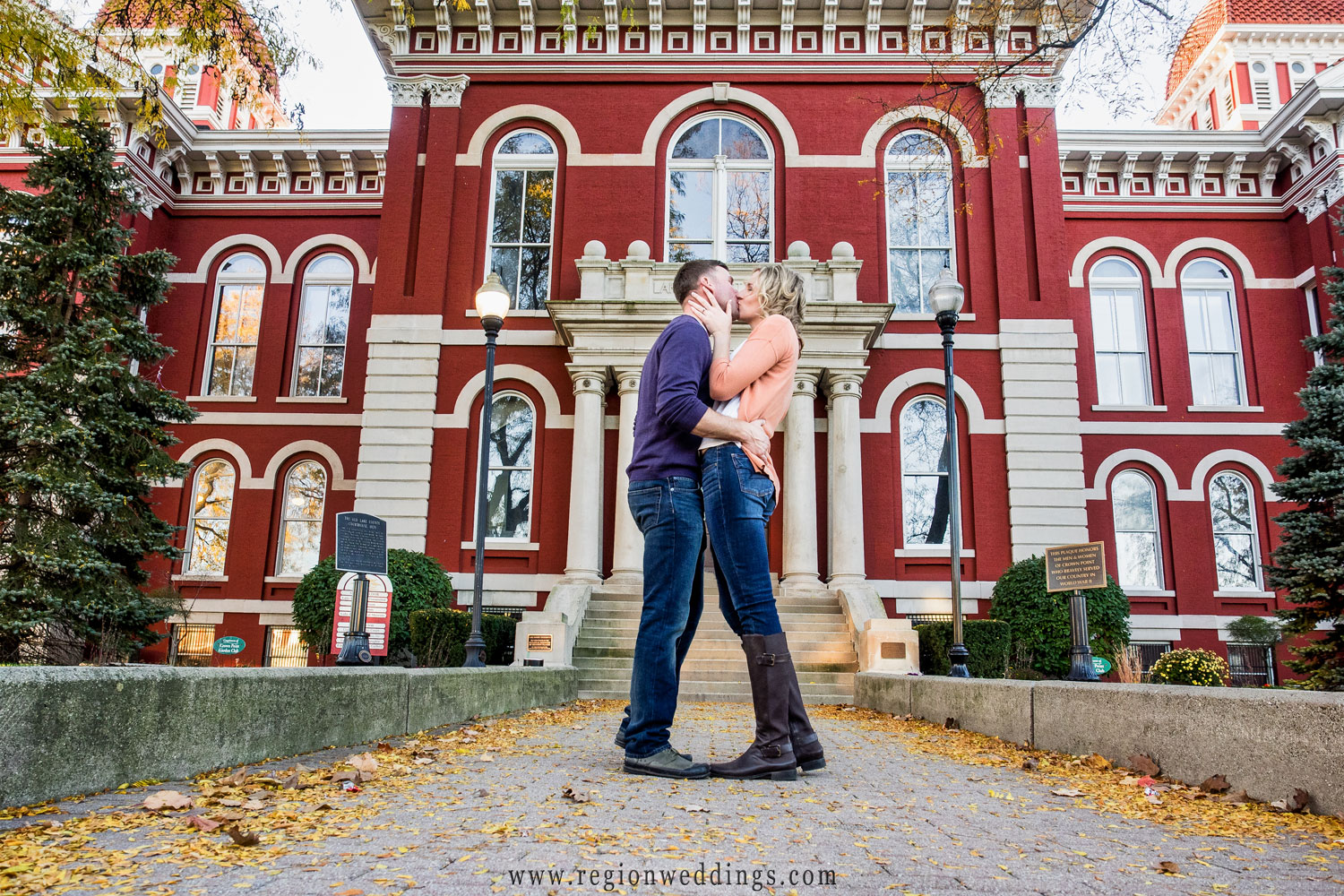 A couple in love kiss romantically at the steps of the Old Crown Point Courthouse.
