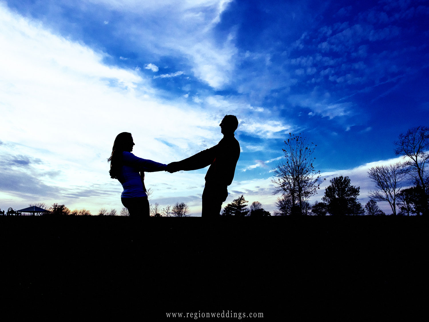 A couple holds hand while leaning away from each other against a blue sky.