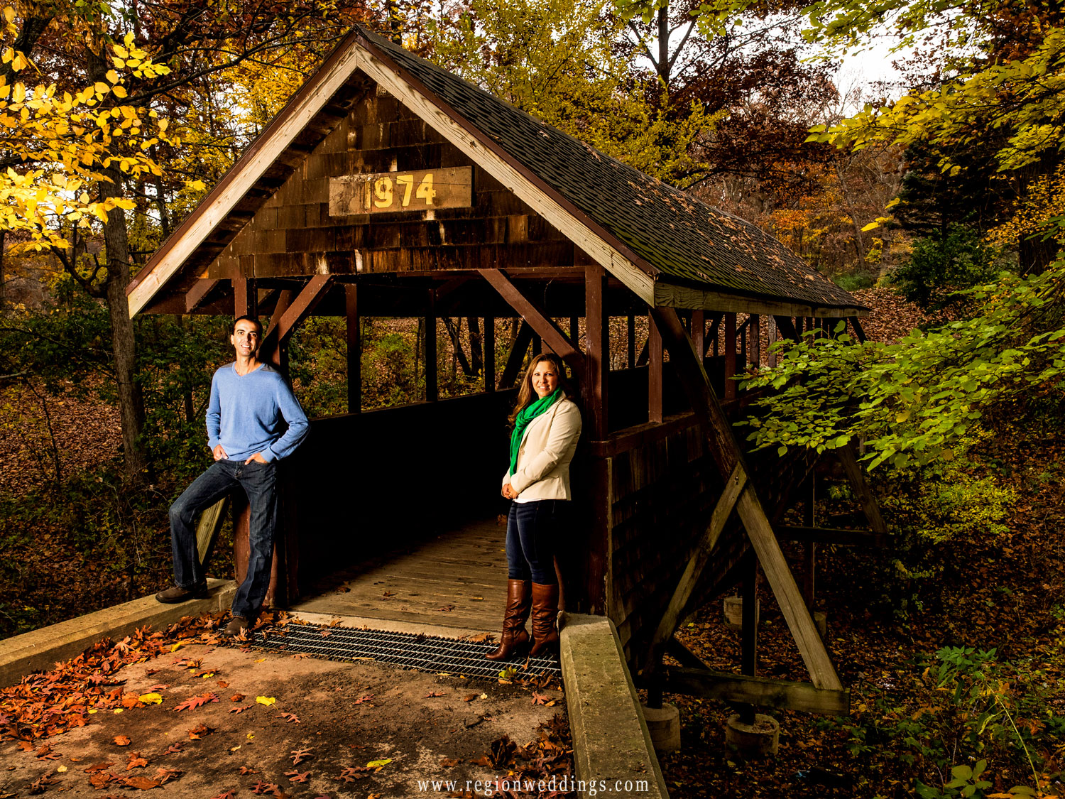 An engaged couple next to a covered bridge for a Fall engagement photo in Cedar Lake, Indiana.