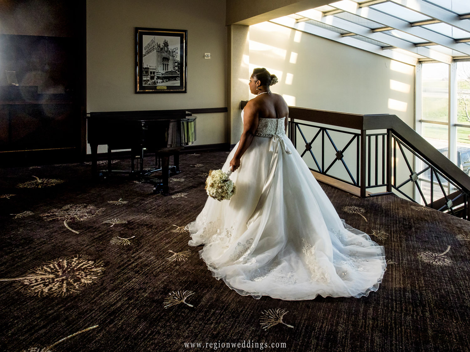The bride shows off the back of her wedding dress in the hotel lobby in Merrillville.