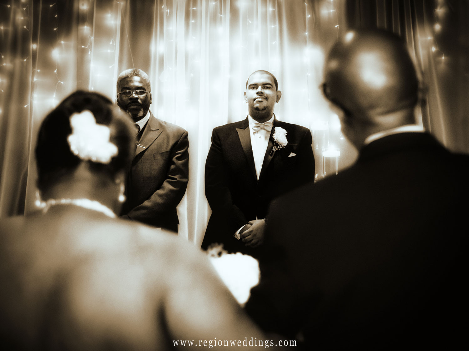 The groom watches his bride come down the aisle in her Father's arms.