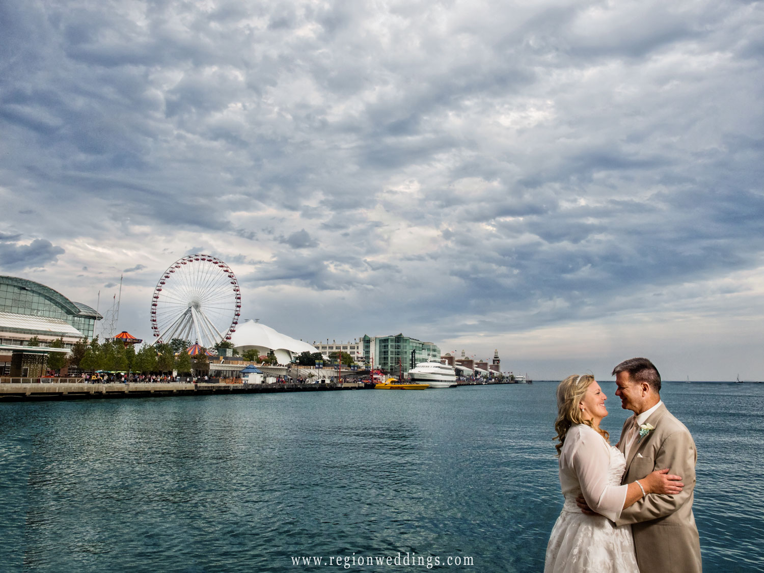 The bride and groom embrace with the ferris wheel at Navy Pier in the background.