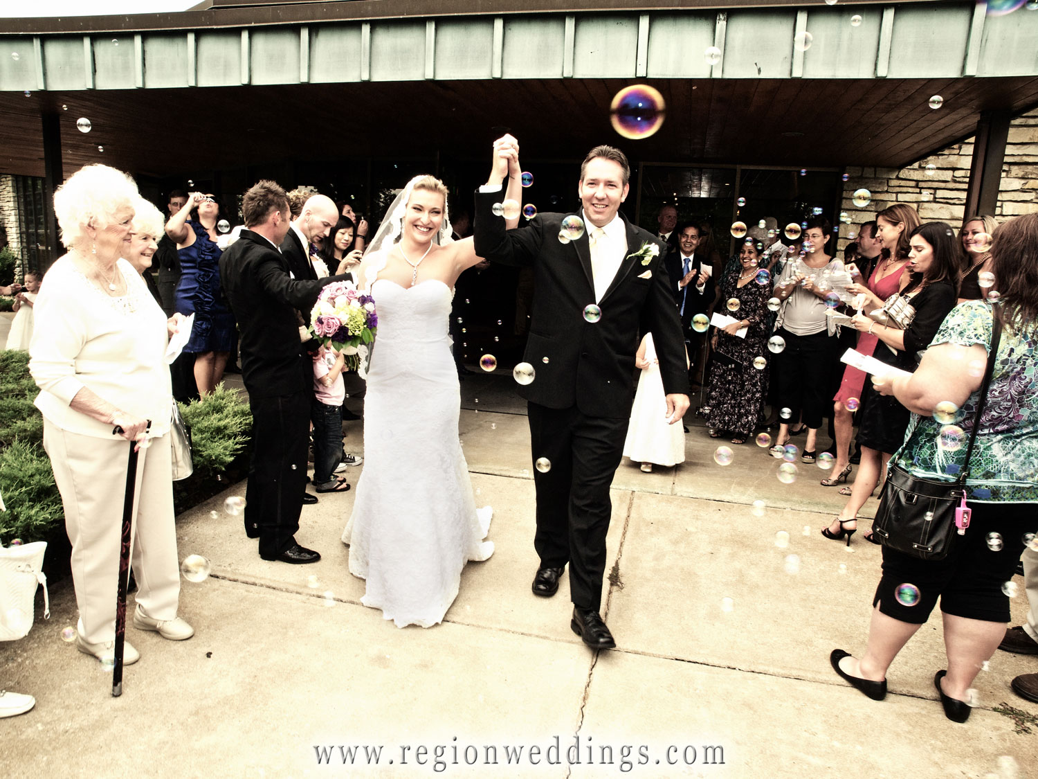 The bride and groom exit Our Lady of Grace underneath multi colored bubbles.