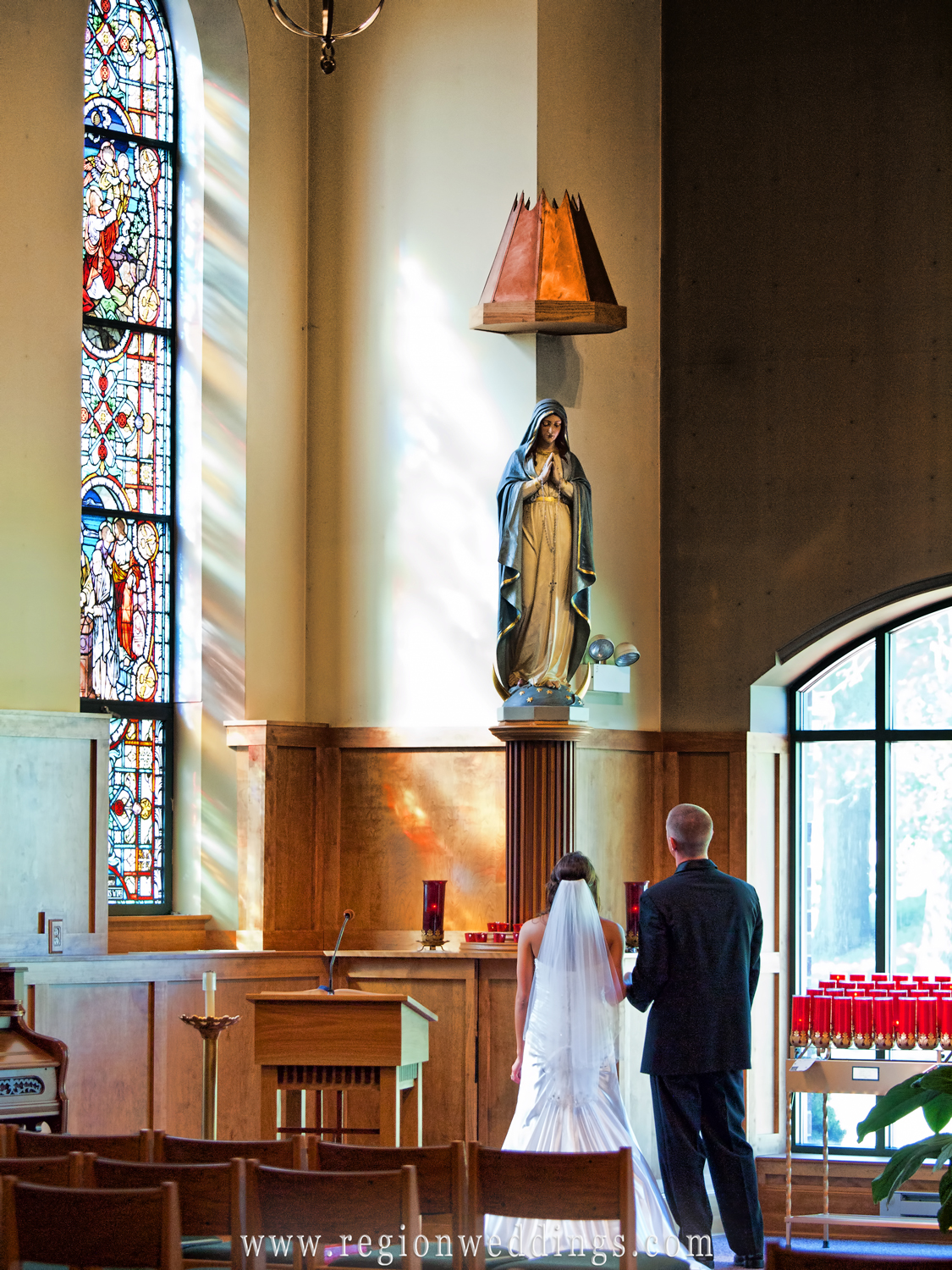 The bride and groom pray underneath the statue of Mary at St. Michael's Church.