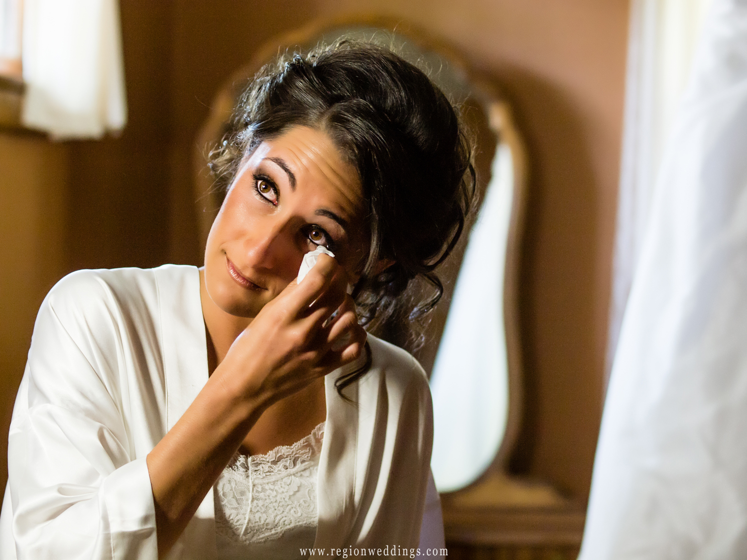 The bride wipes away happy tears on the morning of her wedding.