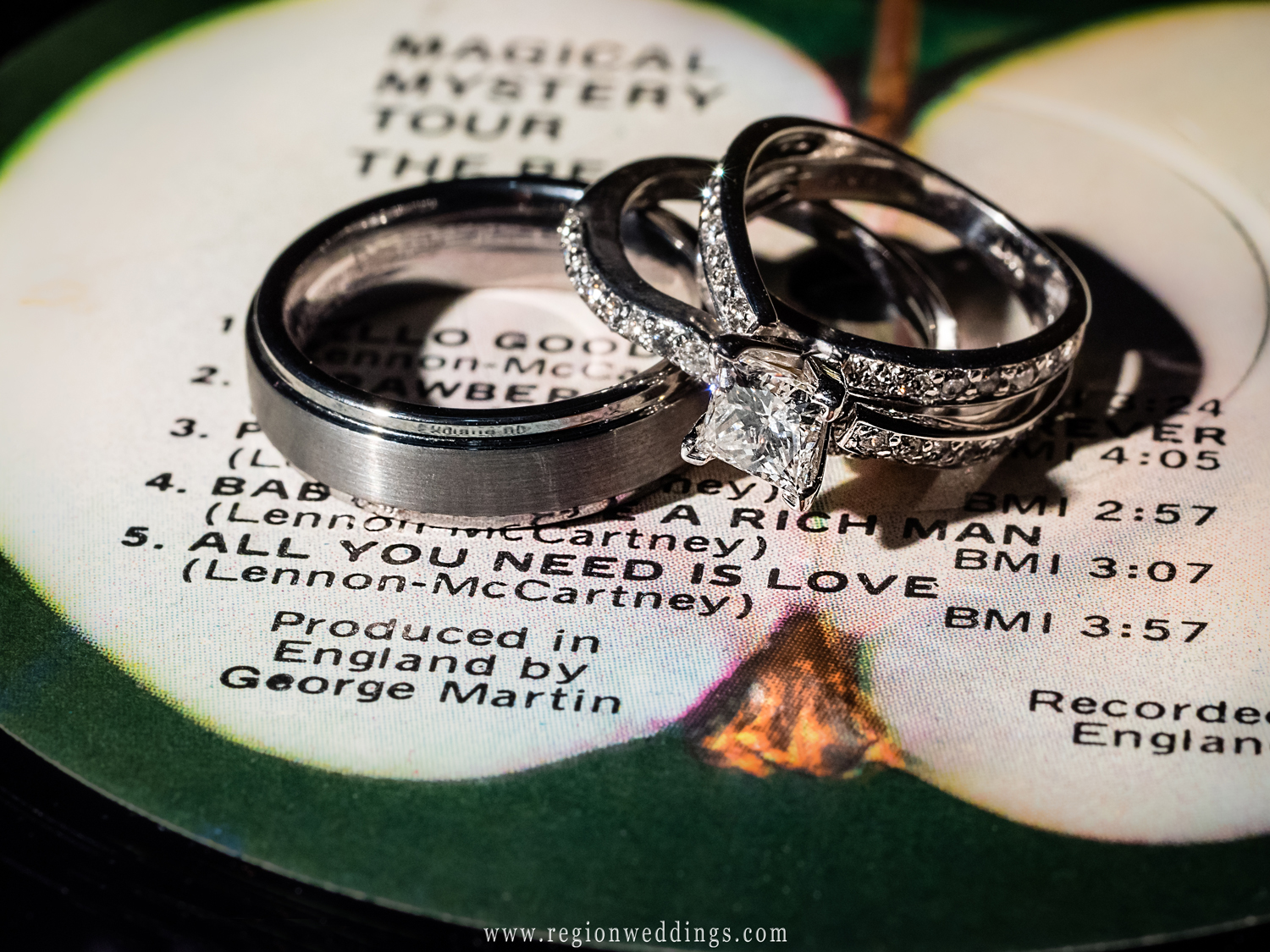 Wedding rings sit atop The Beatles album next to the song All You Need Is Love.