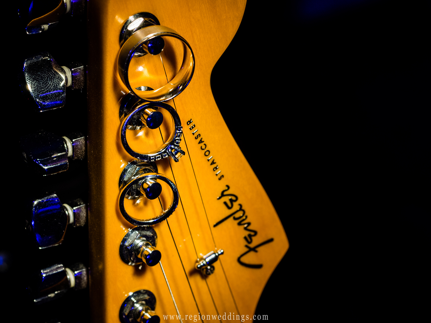 Wedding rings hang from a Fender Stratocaster guitar.