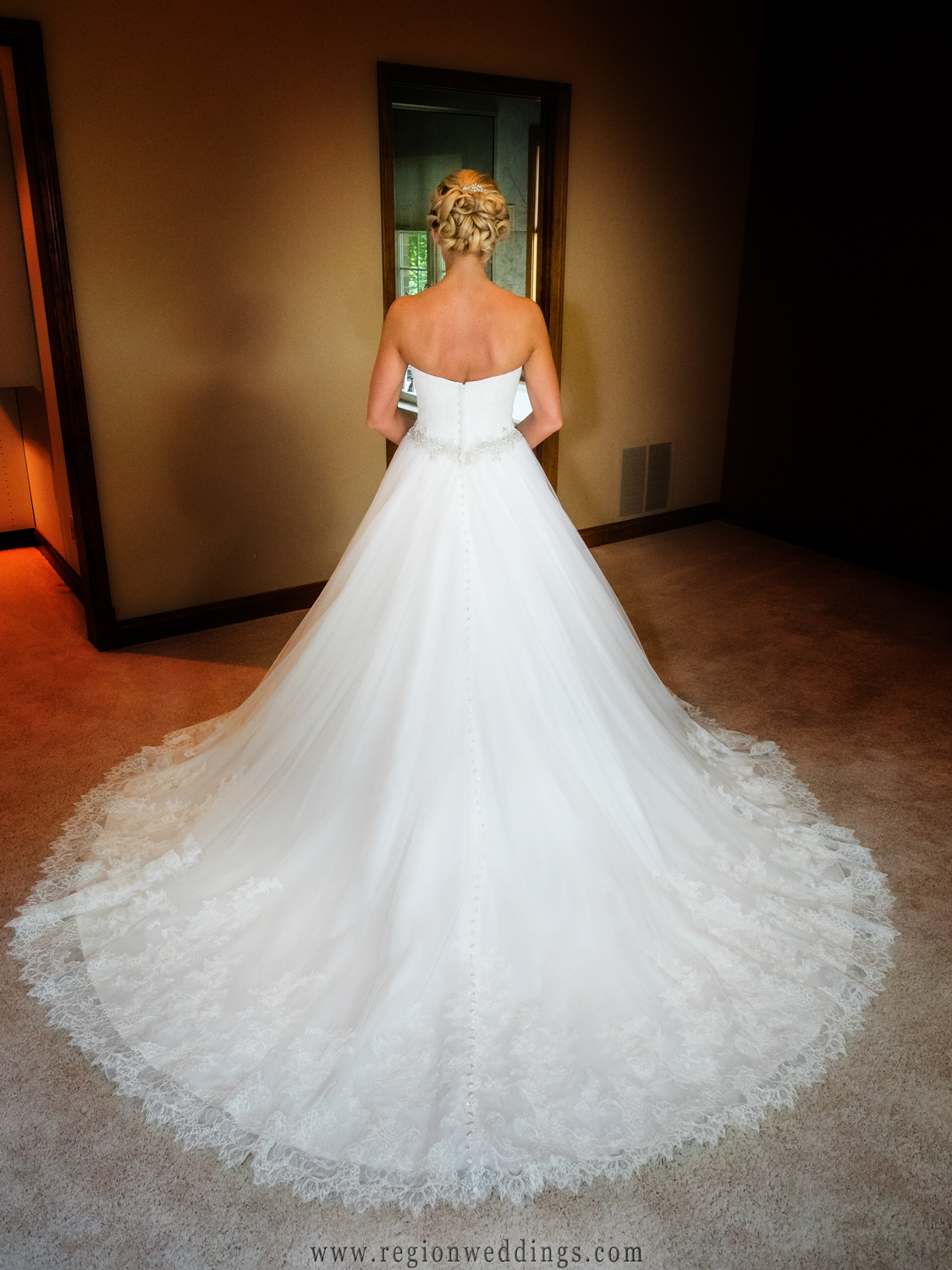 The bride shows off the back of her dress.