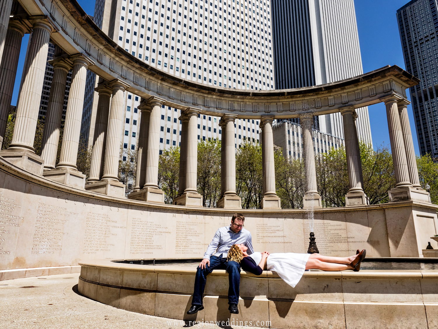 A couple relaxes in front of the Millennium Park fountain in Chicago.