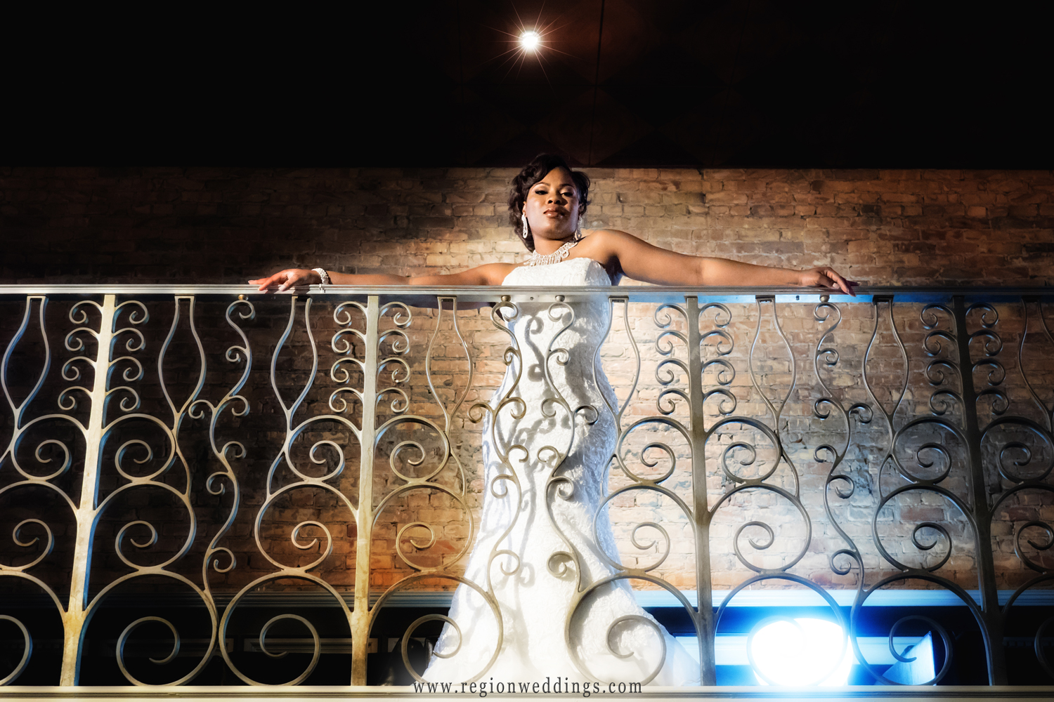 The bride stretches across the balcony railing at The Allure.