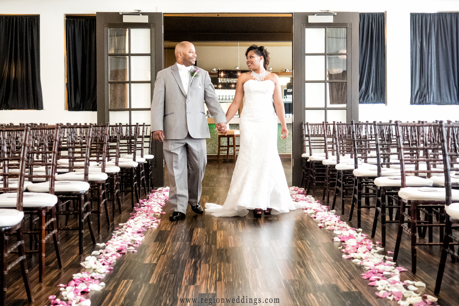 The bride and groom stroll through the center aisle of The Allure between pink and white petals.