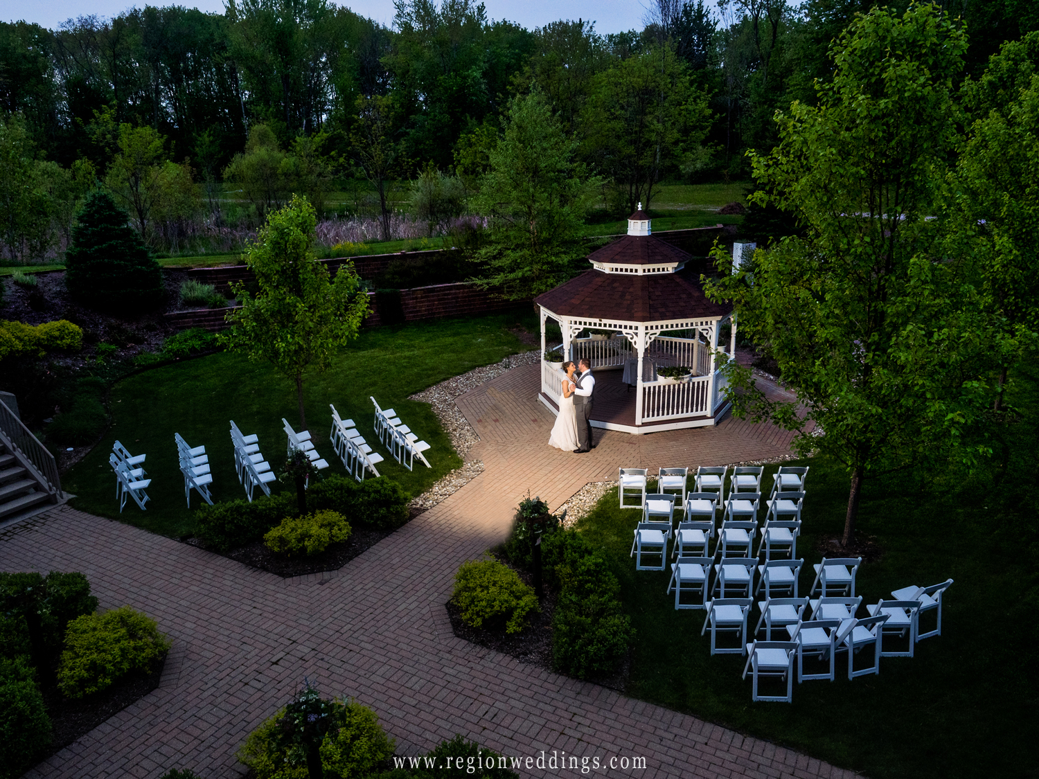 The bride and groom dance at twilight in front of the gazebo at Trinity Hall.