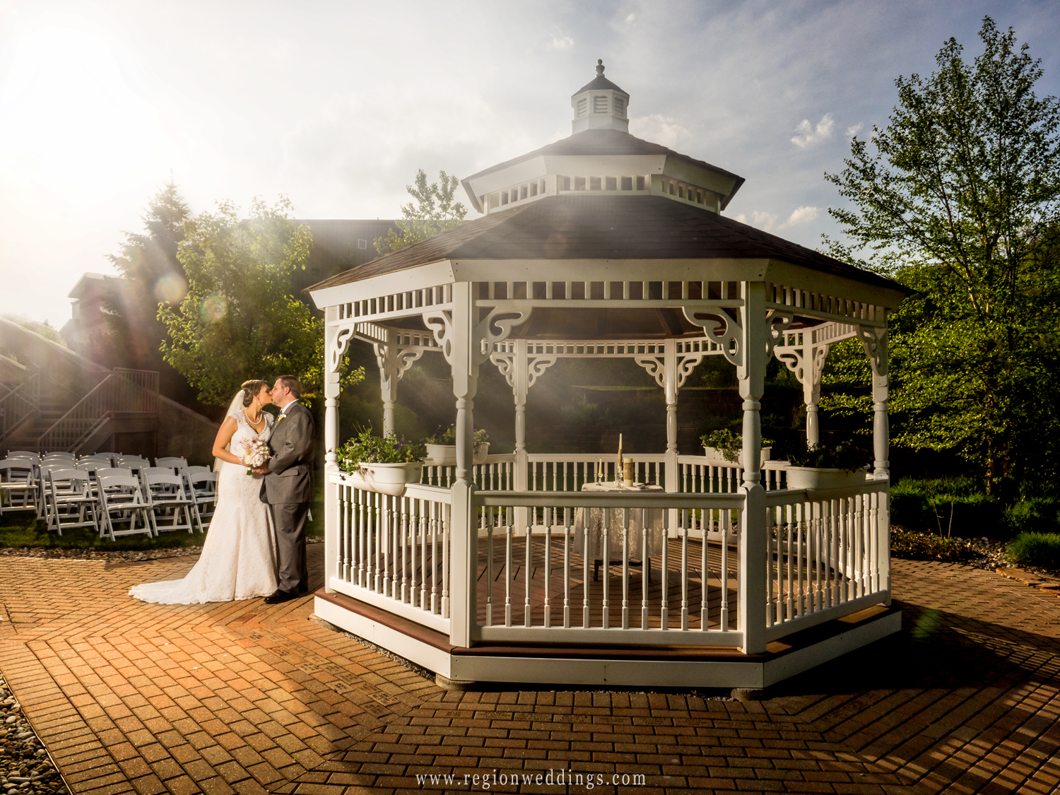The bride and groom kiss by the gazebo as sun rays are cast upon them.