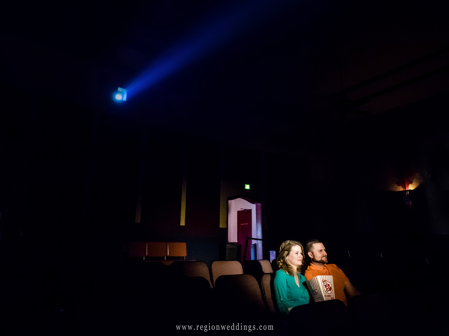 A couple watches a film at the Art Theater for their engagement photos.