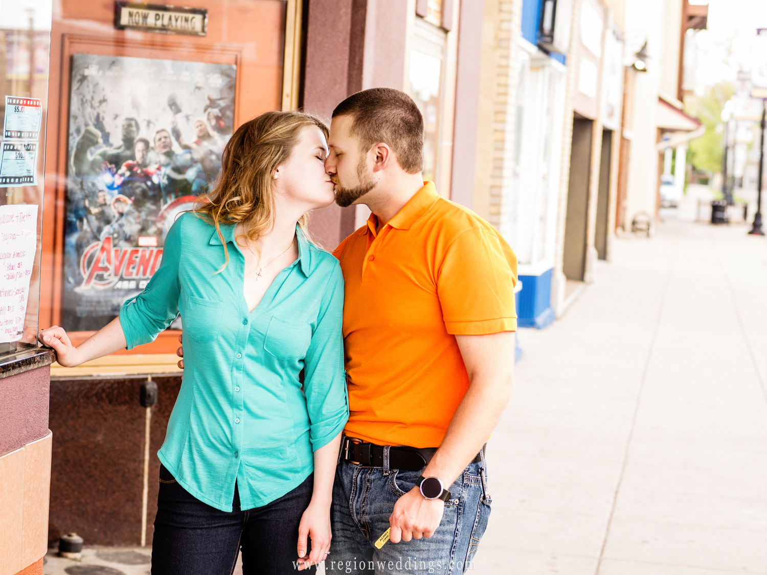 A couple kisses outside the movie theater for their engagement photo.