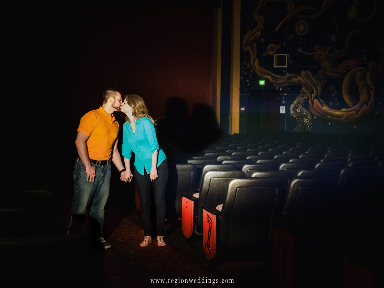 A young couple kisses on the way out of the movie theater.