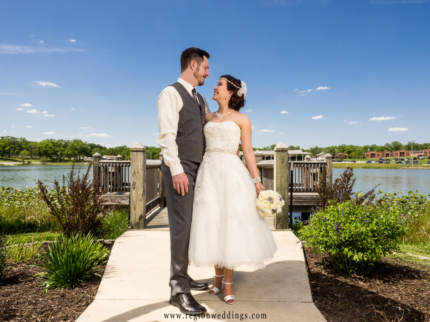 Bride and groom look at each other blue skies at the edge of the pier at Lake County Fairgrounds