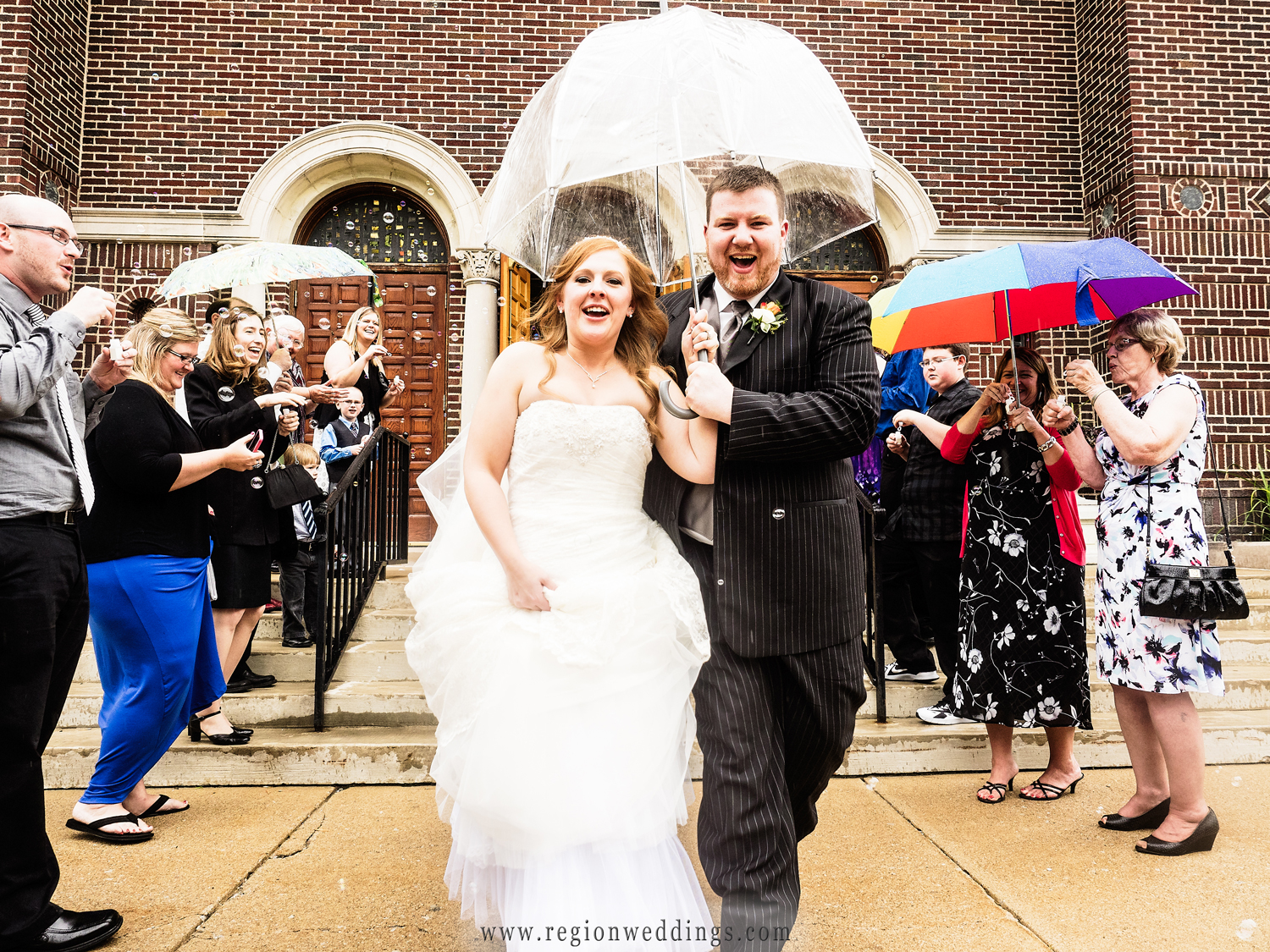 Bride and groom exit the church amidst bubbles with an umbrella to keep dry from the rain.
