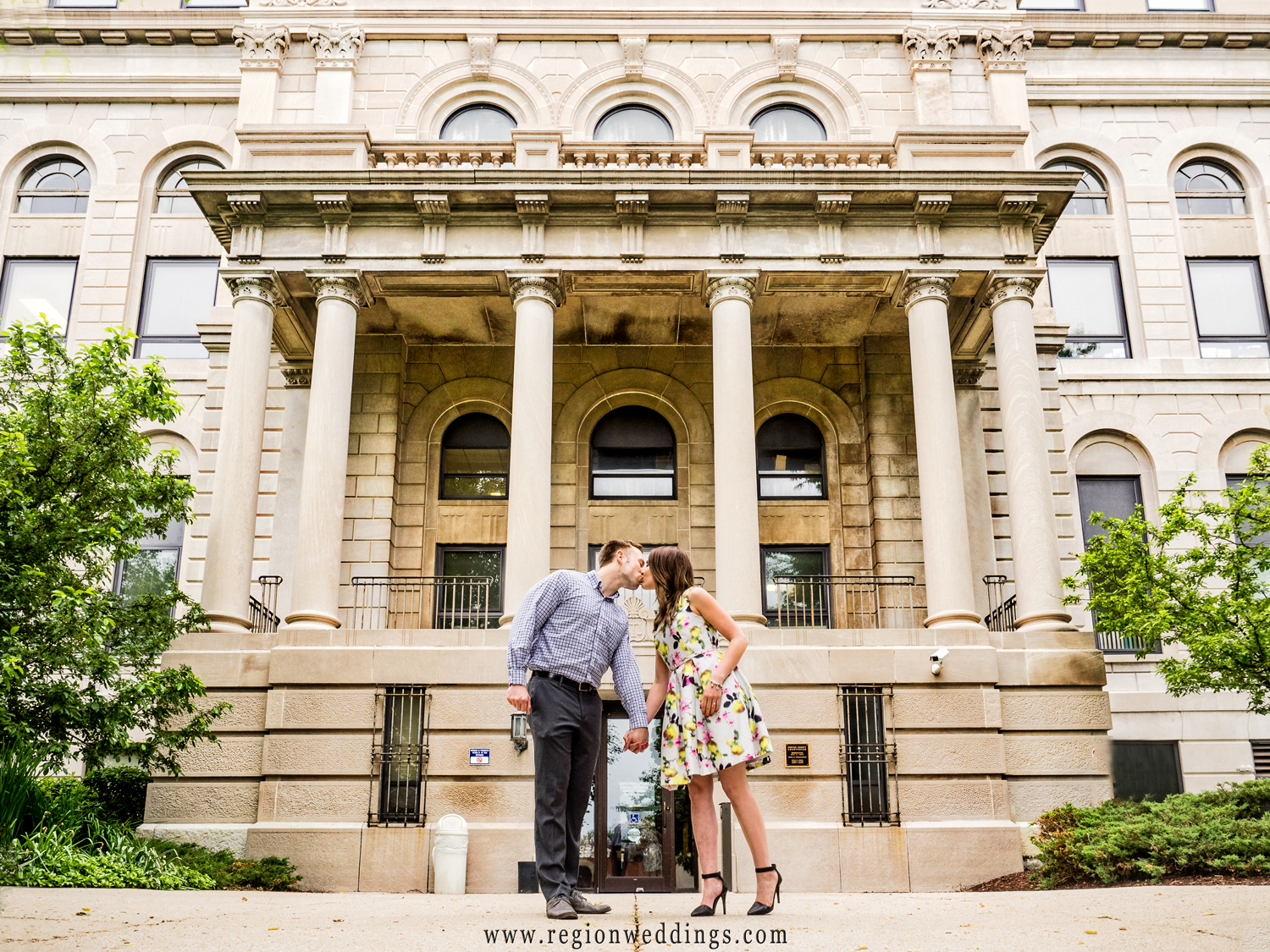 A couple kisses in front of the Porter County Courthouse for their engagement photo.