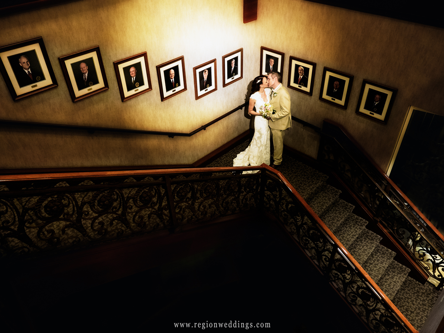 The bride and groom share a romantic kiss on the stairwell at Sand Creek Country Club in Chesterton, Indiana.