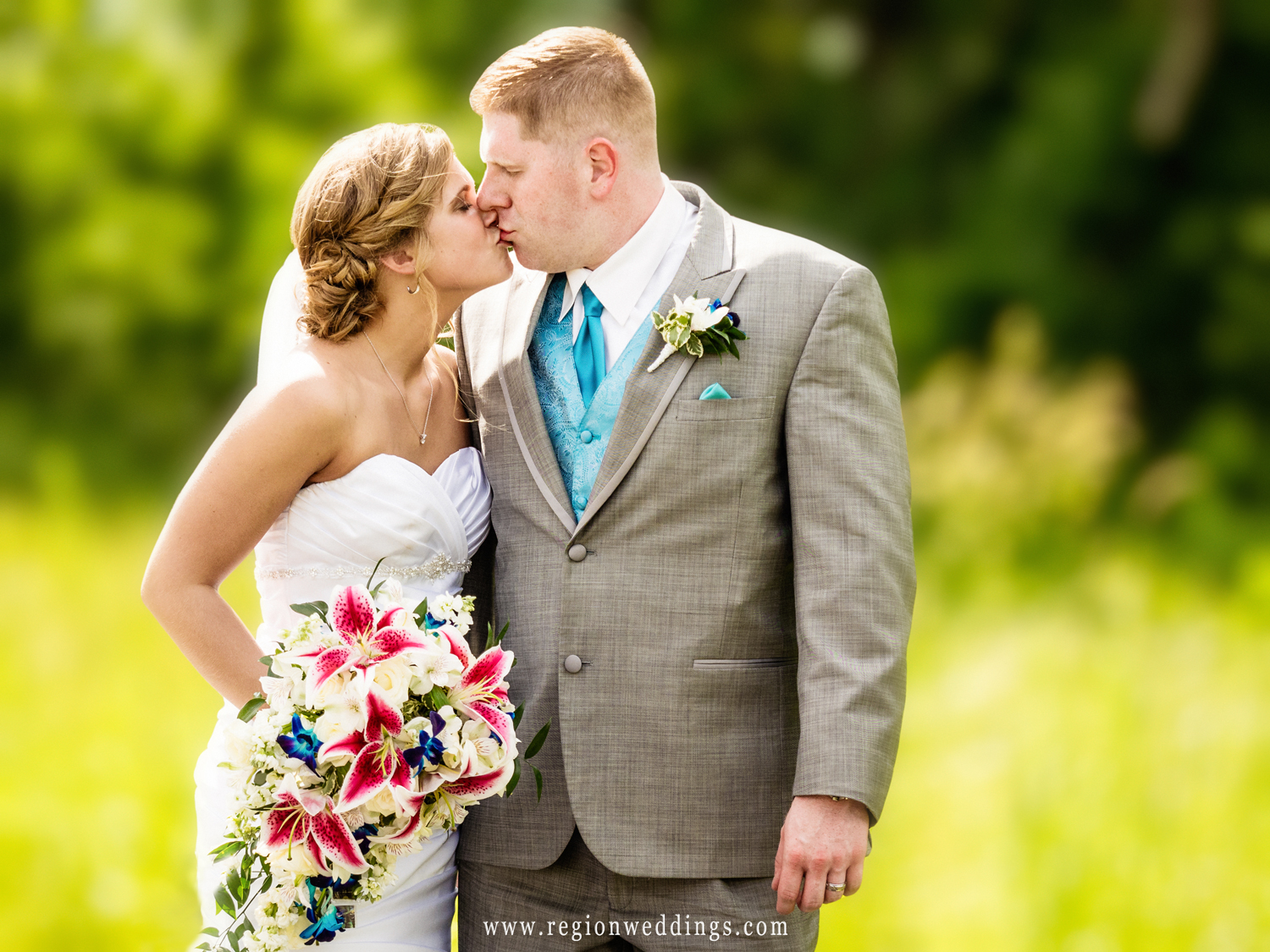 The bride and groom kiss as the late day sun shines upon them.